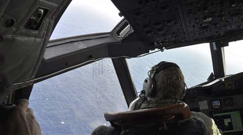 A crewman on a Royal New Zealand Air Force P-3 Orion Rescue Flight 795 searches for debris from the missing Malaysia Airlines Flight MH370, in southern Indian Ocean. (AP)