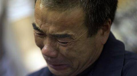 Feng Zhishang cries as family members mark the birthday of his son Feng Dong, a passenger onboard the Malaysia Airlines flight MH370 at a hotel where relatives gather to wait for news of the missing plane in Beijing. (AP)