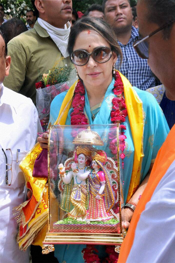 Hema Malini carries a Radhe Krishna idol during her election campaign in Mathura on Monday. (PTI)