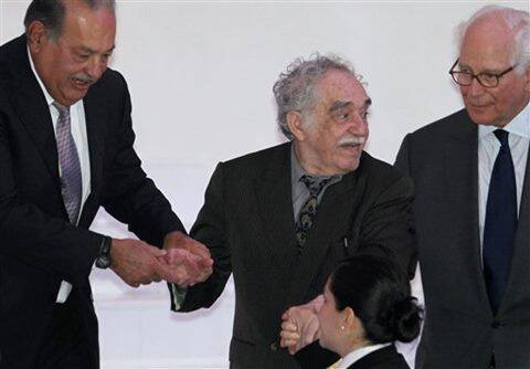 In this March 1, 2011 file photo, Mexican telecom tycoon and world's richest man Carlos Slim, left, and British financier Sir Evelyn de Rothschild, right, help Nobel laureate Gabriel Garcia Marquez at the inauguration of the Soumaya Museum's new home in Mexico City.