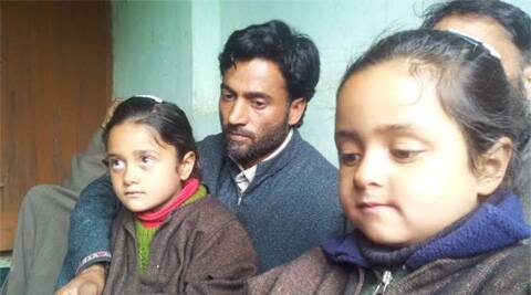 "Javaid with his daughters Munaza and Mehak. ""The government should at least let my children go back,"" he says. (Photo: Shuaib Masoodi)"