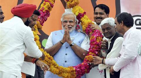 BJP Prime Ministerial candidate Narendra Modi being garlanded during an election rally in Shivpuri, Madhya Pradesh on Saturday. (PTI Photo)
