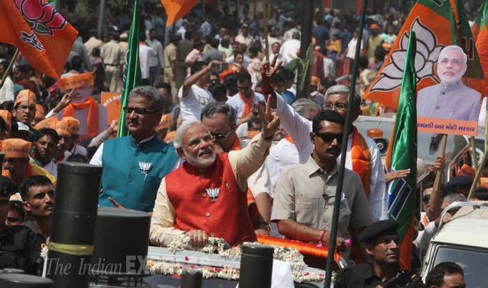 BJP PM candidate Narendra Modi waves to supporters from an open jeep on his way to the collector's office to file his nomination form for Vadodara Lok Sabha seat. (IE Photo: Javed Raja)
