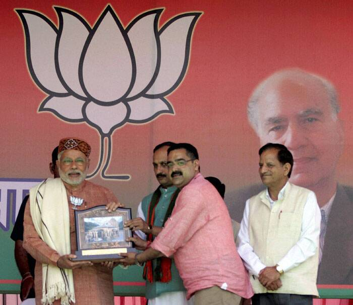 "Referring to price rise, BJP's Prime Ministerial candidate said, ""Congress had promised in its 2009 manifesto that it will bring down prices within 100 days. So is it not a 'dhokapatra' ?"" <br /> BJP PM candidate Narendra Modi presented with a memento by party officials during a BJP rally in Palampur, Himachal Pradesh on Tuesday. (PTI)"