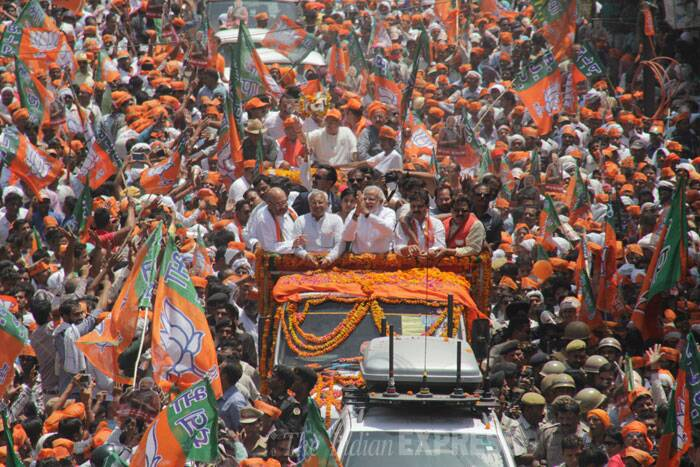 At BHU, he was welcomed by thousands of people as sound of conch shells reverberated the air. The BJP has made elaborate arrangement to make the road show a show of strength and create a momentum for the party's Prime Ministerial candidate. <br /><br /> The BJP supporters had started gathering along Modi's route since morning to have a glimpse of Modi. Large number of people were seen on rooftops and balconies of all buildings along Modi's route. (IE Photo: Anand Singh)