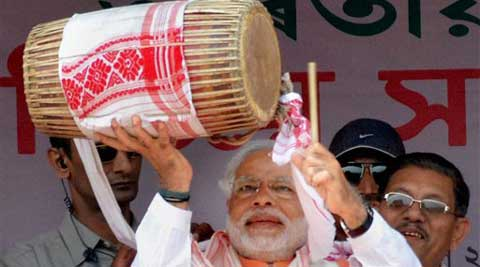 BJP Prime Ministerial candidate Narendra Modi plays traditional Assamese Dhol during an election campaign rally at Mongoldoi, Assam on Saturday. (PTI)