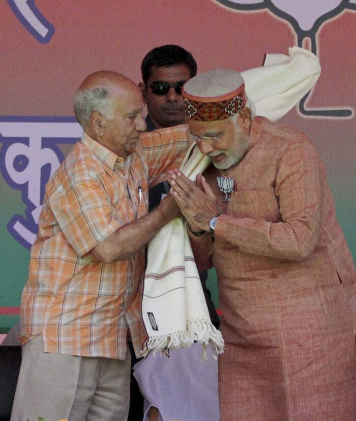 "Asking people to give BJP a chance at the Centre, Modi said, ""You have given 60 years to the ruler (Congress), now give me 60 days to serve you. The country does not need a ruler, it needs a ""sevak"" (servant). <br /> Shanta Kumar BJP candidate from Kangra  honours Narender Modi with shawl during the BJP rally at Palampur on Tuesday. (PTI)"