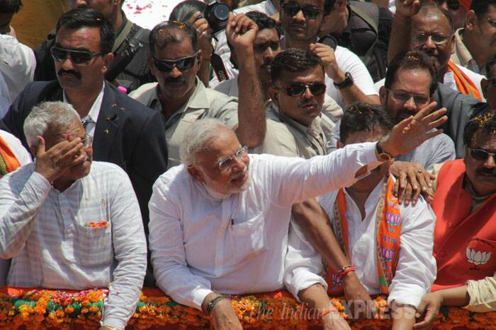 BJP's Prime Ministerial pick Narendra Modi arrived in Varanasi to a rousing welcome from party supporters to file his nomination for the mega electoral battle in the holy city where he has been challenged by AAP leader Arvind Kejriwal. <br /><br /> Narendra Modi waves at supporters at a road show before filing his nomination papers in Varanasi. (IE Photo: Anand Singh)