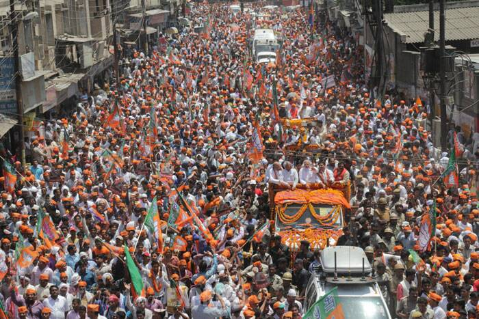 BJP units in all the 90 wards in the city reached the venue of the road show by carrying out procession from their respective wards. Modi will carry out a two-km long road show before filing nomination at the District Magistrate's office.  (IE Photo: Anand Singh)