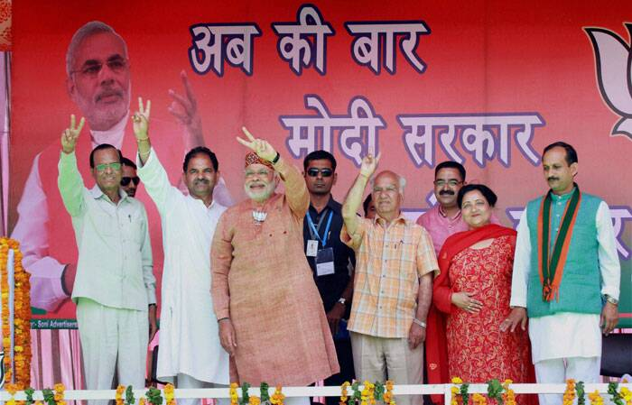 BJP PM candidate Narendra Modi with party candidate from Kangra Shanta Kumar(3rd from R) and other party leaders during an election rally in Palampur, Himachal Pradesh on Tuesday. (PTI)