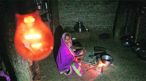 Mogra Padvi, 50, cooks in dim light at her home in Nandurbar's Valamba hamlet.  Pradeep Kocharekar