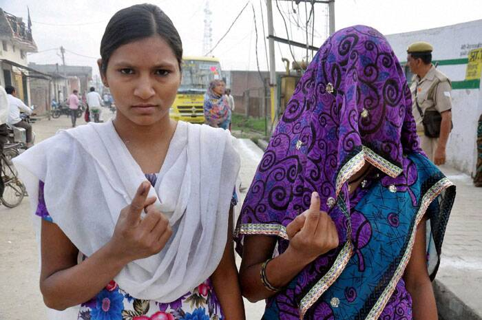 Women voters flaunt their inked fingers after casting their vote in Moradabad on Thursday. (PTI)
