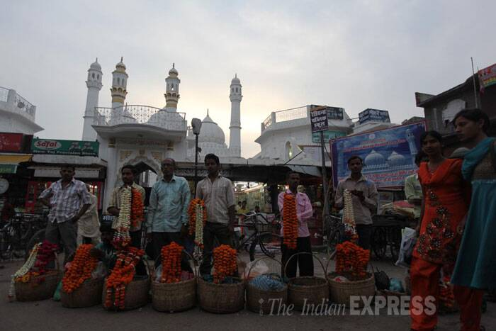 Florists stand outside the main city mosque at the Chowk in Faizabad, where sectarian riots broke out in 2012 during a Hindu procession and spread to the neighbouring villages. (IE Photo: Tashi Tobgyal)