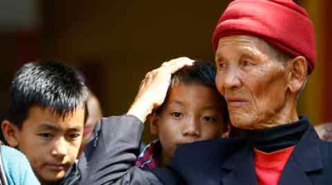 Father and sons of Nepalese mountaineer Ang Kaji Sherpa, killed in an avalanche on Mount Everest, wait for his body to arrive at Sherpa Monastery in Katmandu, Nepal, Saturday. (AP Photo)