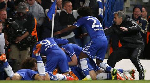 Chelsea's Demba Ba (hidden) celebrates with coach Jose Mourinho (R) and team mates after scoring the second goal for the team during their Champions League match against Paris St. Germain. (Reuters)