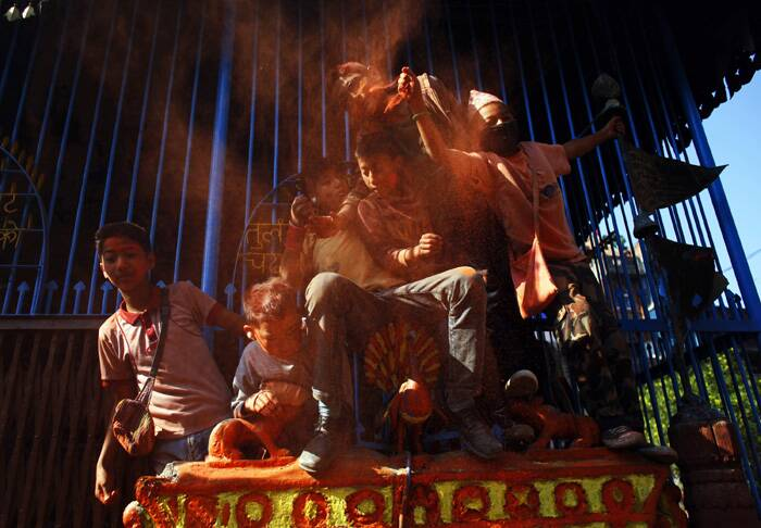 All government offices, private offices and educational institutions were closed to mark the Nepalese new year, which starts from mid-April.<br />Nepalese children throw sindoor to celebrate Sindoor Jatra festival in Bhaktapur. (AP)