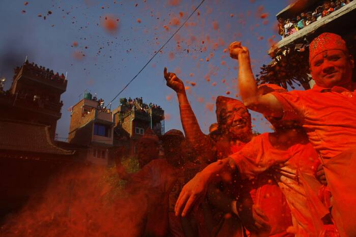 Major tourist hubs here, mainly Thamel, Durbarmarg and Hanumandhoka Durbar Square were jam-packed with tourists as well as Nepalese youths, who gathered there for celebrations. <br />Nepalese throw sindoor to celebrate Sindoor Jatra festival in Bhaktapur. (AP)