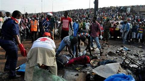 Rescue workers collect the bodies of victims as people gather at the site of a blast at the Nyanya Motor Park, about 16 kilometers (10 miles) from the center of Abuja, Nigeria, Monday, April 14, 2014. (AP)
