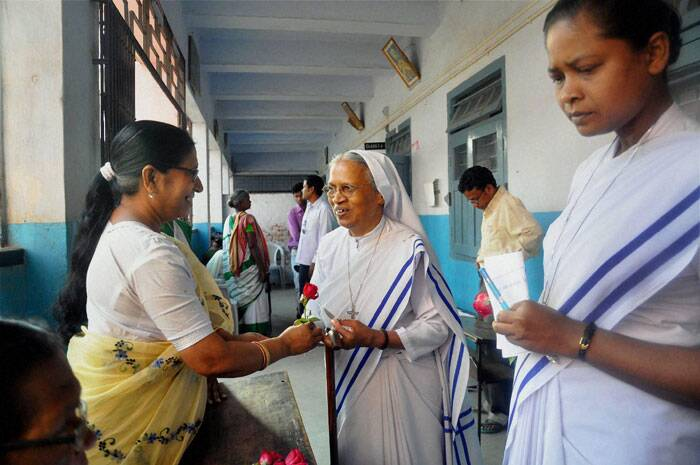 An election official distributes roses to Catholic Nuns during fifth phase of Lok Sabha elections in Ranchi, Jharkhand on Thursday. (PTI)