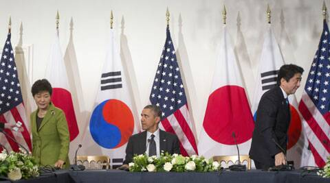 U.S. President Barack Obama watches South Korean President Park Geun-hye and Japanese PM Shinzo Abe move to their seats at the opposite ends of the table to start their trilateral meeting shortly after they sat together. (AP)