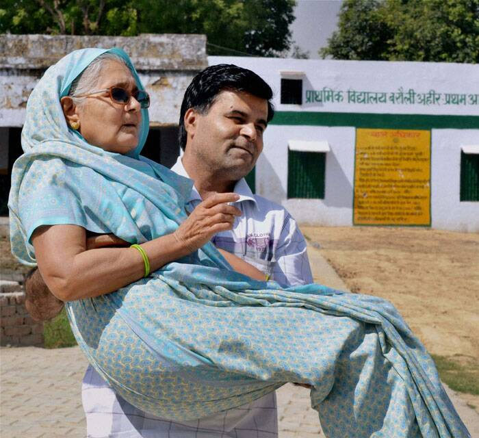 A son carries his  mother to vote, at a polling station in Agra on Thursday. (PTI)