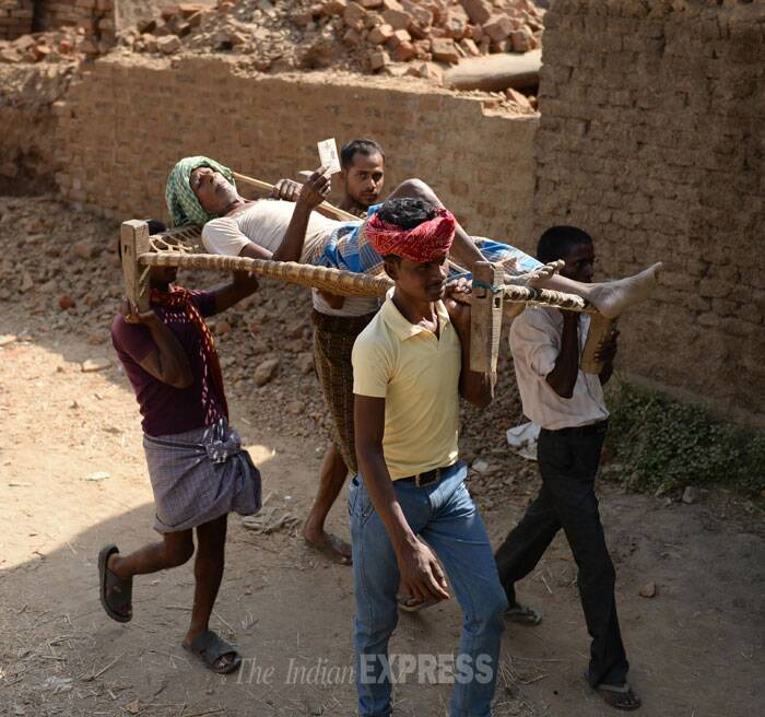 An old man is being taken by other villagers to the polling booth in a constituency in Bihar. (IE Photo: Alok Jain)