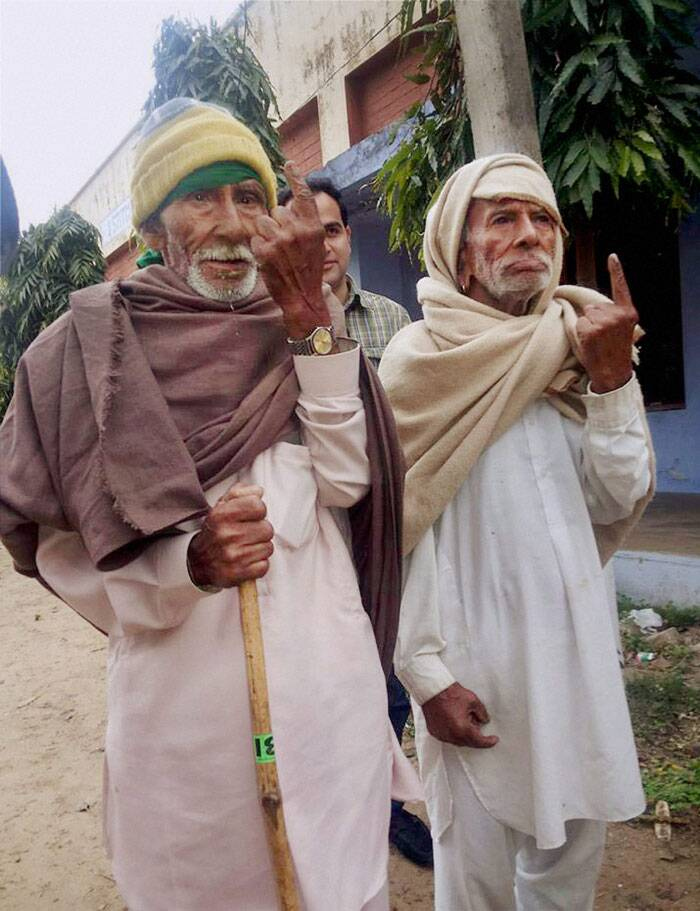 An elderly voter shows his inked finger after casting his votes in Hiranagar near the international border in Kathua on Thursday. (PTI)
