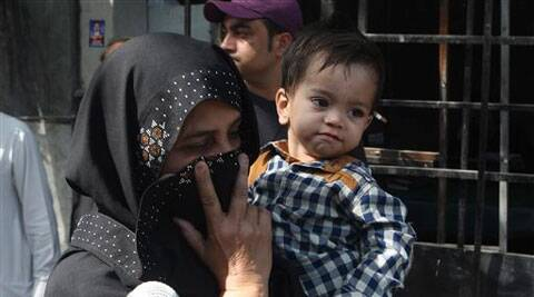 An unidentified family member holds a nine-month-old boy, trying to avoid media as they leave after the boy's court appearance in Lahore, Pakistan on Saturday. (AP)