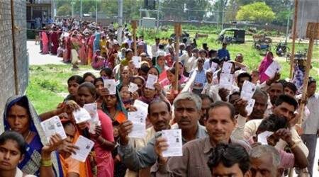 People wait in long queues to cast their votes at a polling station for Lok Sabha elections.