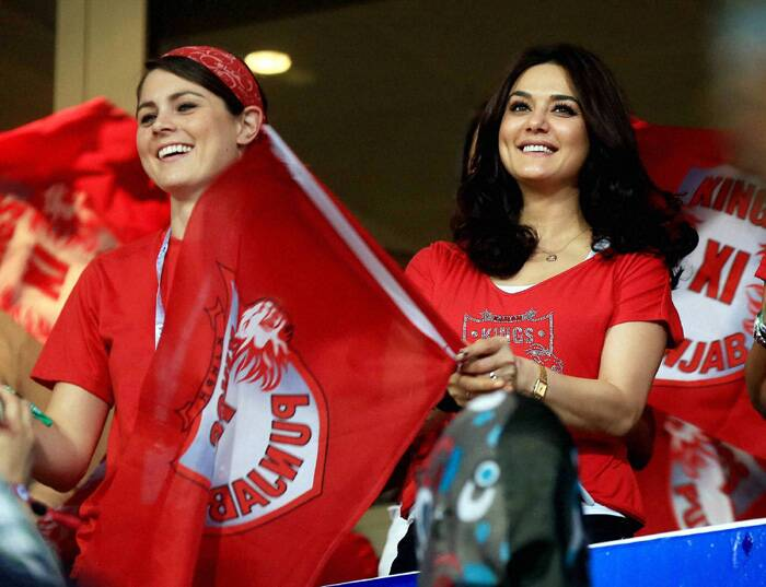 Kings XI Punjab owner and actress Preity Zinta waves her tems flag  as her team's unbeaten run in this year's tournament continues. (PTI/BCCI) <br />IPL 7: Sakshi Dhoni, R Ashwin's wife cheer for CSK