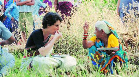 Priyanka Vadra shares a meal with a woman in Rae Bareli on Tuesday. PTI