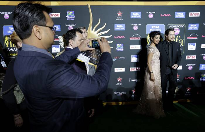 A fan clicks a picture as Priyanka Chopra and Kevin Stacey pose for the photogs. (AP)