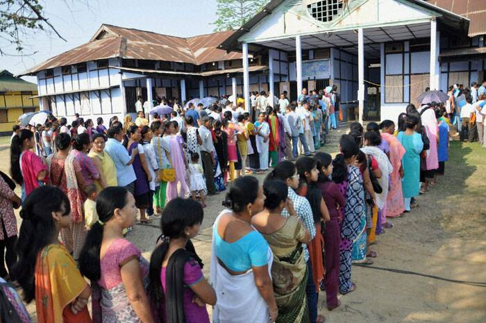 People wait in queues to cast their votes for Lok Sabha polls at a polling station, at Diphu in Karbi Anglong district of Assam on Saturday. (PTI)