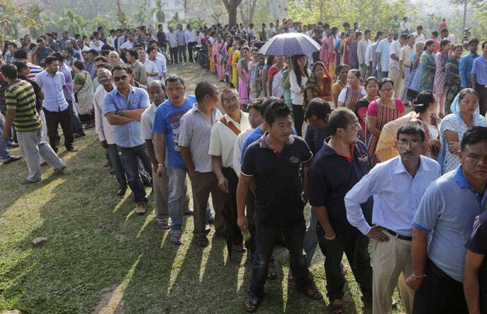 People stand in queues to cast their votes at a polling booth in Diphu, in the northeastern Indian state of Assam on Saturday. (AP)