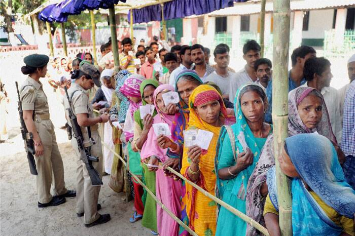 Voters standing in a queue to cast their votes in Araria on Thursday. (PTI)