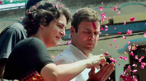 Congress Vice President Rahul Gandhi shares with his sister Priyanka Gandhi 'Prasad' offered by a supporter during his nomination filing procession in Amethi on Saturday. (PTI)