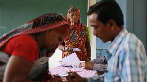 A polling officer checks the identity of a voter, as another awaits her turn at a polling station in Rajnandgaon. (PTI)