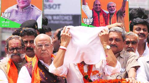 BJP candidate Rajnath Singh puts wet cloth on his face as Goa CM Manohar Parrikar and local MP Lalji Tondon look on during a roadshow in Lucknow on Sunday. Pramod Singh