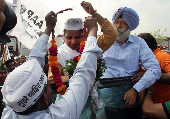 AAP leader Rakhi Birla during the road show in support of the party candidate H S Phoolka (right) passes under the historic Clock Tower in Ludhiana. (Express Photo: Gurmeet Singh)
