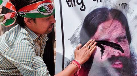 A Congress supporter blackens a poster of Baba Ramdev who made controversial statements on Rahul Gandhi, in Bikaner on Saturday. (PTI)