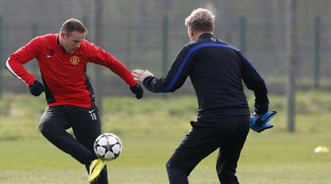 Manchester United's Wayne Rooney (L) controls a ball next to manager David Moyes during a training session at the club's Carrington training complex in Manchester (Reuters)