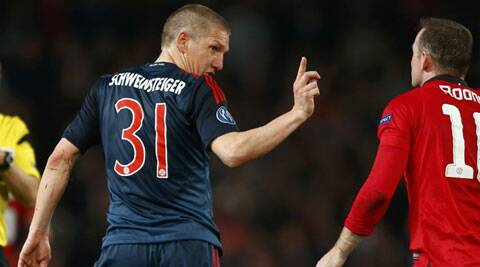 Bayern Munich's Bastian Schweinsteiger gestures to Manchester United's Wayne Rooney (R) after fouling him during their Champions League quarter-final first leg match on Tuesday. (Reuters)