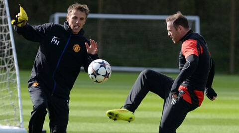 Manchester United's Wayne Rooney kicks a ball near coach Phil Neville (L) during a practice session at the club's Carrington training centre in Manchester on Tuesday. (Reuters)