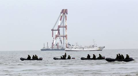 South Korean navy personnel on boats search passengers of the sunken ferry Sewol in the water off the southern coast near Jindo, south of Seoul. (AP)