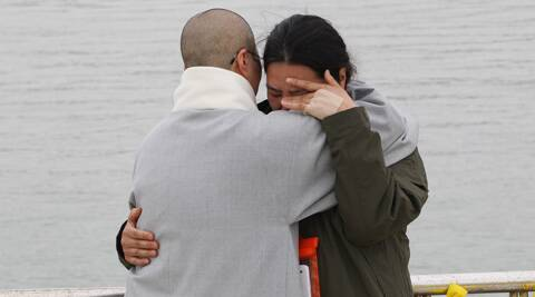 A relative of a passenger aboard the sunken ferry Sewol is consoled by a Buddhist nun, left, as she waits for news on her missing loved one at a port in South Korea. (AP)