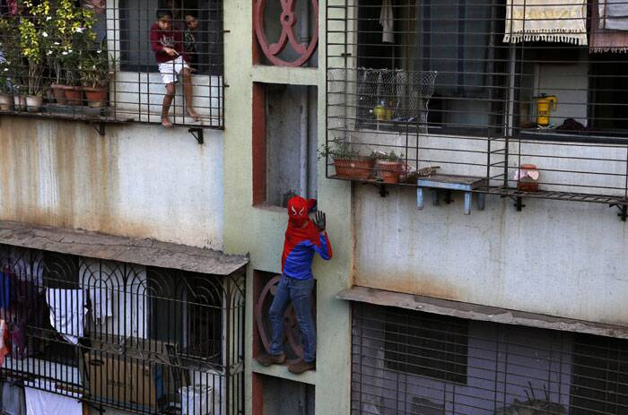 Residents watch as Gaurav Sharma, locally known as Indian Spiderman who is contesting as an Independent candidate in the upcoming parliamentary elections, climbs a building as part of his campaign in Mumbai on Thursday. <br /> The Lok Sabha elections have kicked off from April 7 that many observers see as the most important election in more than 30 years in the world's largest democracy. (AP )
