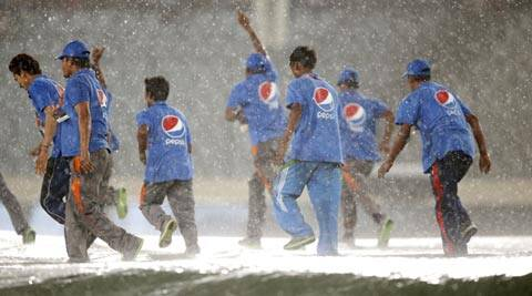 Groundsmen run to cover the pitch as it rains during the ICC Twenty20 Cricket World Cup semifinal match between Sri Lanka and West Indies (AP)