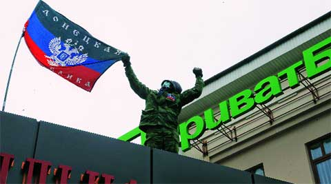 A pro-Russian activist puts a 'Donetsk Republic' flag over a building Monday. AP
