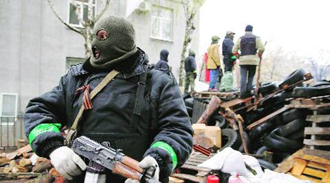 An armed man stands next to a barricade in front of the police headquarters in Slaviansk on Sunday.  (REUTERS)