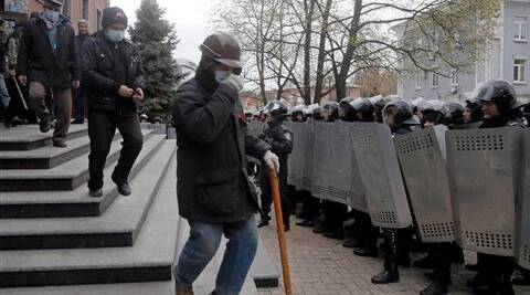 Riot police officers watch as masked pro-Russian activists leave the regional prosecutor's office after their talks, in Donetsk, Ukraine, on Saturday. (AP)